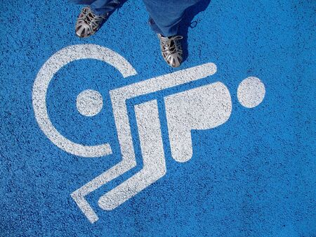 valid: Logo for disabled on parking lot with valid person feet from above Stock Photo