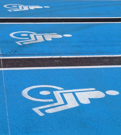 3 Logos for disabled on parking lot on supermarket photo