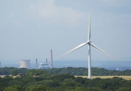 powerplants: windturbine with at background a coal electricity powerplants factory