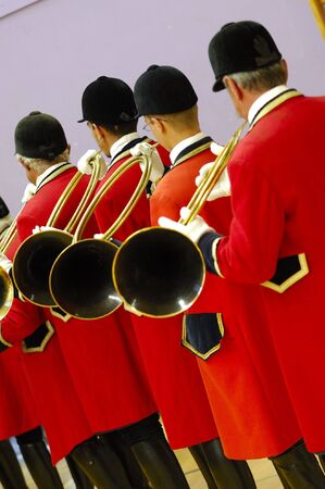 musicians playing on hunting horn and with traditionnal red dress - fox hunting parade Stock Photo