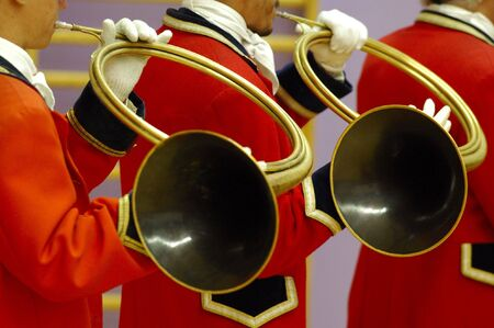 details of musicians group  playing on hunting horn and with traditionnal red dress - fox hunting parade Stock Photo