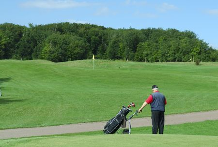 Senior man holding his caddie on a golf course