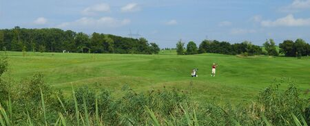 Panoramic view of golf course with a woman playing photo