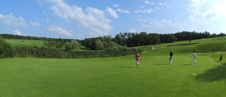Panoramic view of golf course with players photo