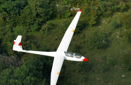 A glider Janus A flying over Alps forest at Challes les eaux France