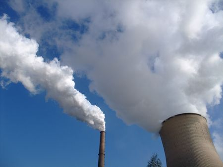 Steam geting out of a cooling tower of a coal power plant into blue sky Stock Photo