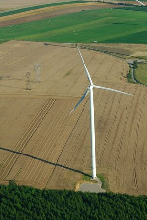 windturbine: Overview of a windturbine and yellow field in France Europe Stock Photo