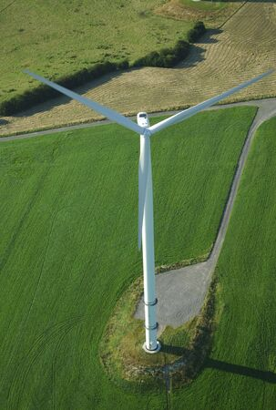 Overview of a lonely  windturbine in green meadow France Europe