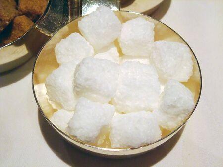 Raw white sugar cubes into a bowl