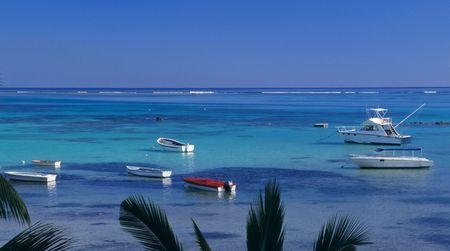 Blue lagoon at Bain Beauf beach with boats. Cape Malheureux, Mauritius Island, Indian Ocean