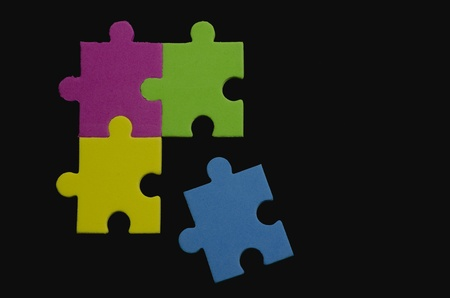 Colorful puzzle pieces over black background representing variety and tolerance Stock Photo