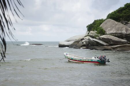 Beachscape with boat in Cabo San Juan del Guia, Tayrona National Park, Colombia