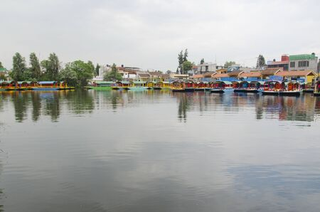 Beautiful scene in Xochimilco, Mexico; trajinera boats on hold and the sky reflected in the water