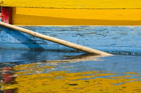 Colorful frame: detail of yellow, blue and red Trajinera boat and its reflection, in Xochimilco, Mexico