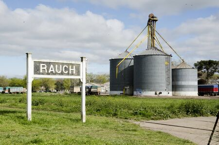 Sign with the name of the village and rural silos, at the train station, in Rauch, Buenos Aires, Argentina