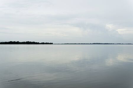 Lake Chascomus, a summer afternoon. The cloudy sky is reflected on the surface of the water. Province of Buenos Aires, Argentina. 免版税图像