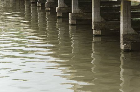 Bottom of a pier and its reflection in the water Banco de Imagens