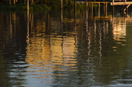 Wooden pier reflected in moving water in the Tigre Delta, in the province of Buenos Aires, Argentina