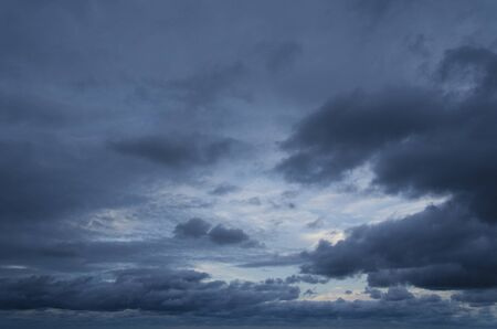 Cloudscape: in the background a small clear blue part, the rest of the image is filled by dark gray clouds that stretch across the sky