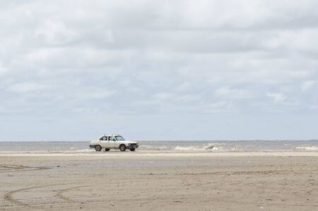 Beach landscape, a car standing in the sand with the sea in the background, in Punta Rasa, Province of Buenos Aires, Argentina