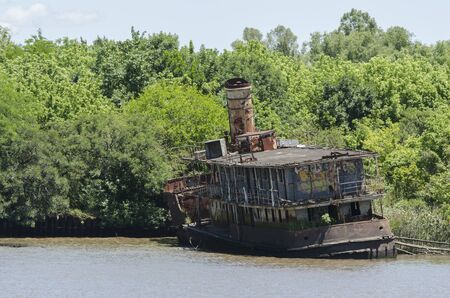 Tigre, Buenos Aires / Argentina; Dec 10, 2015: Old ship abandoned and rusty on the shore of a water channel