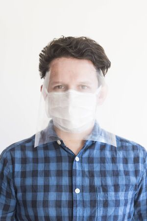 Young man wearing a disposable face mask and a homemade protective mask, to prevent the spread of the coronavirus disease, Covid-19