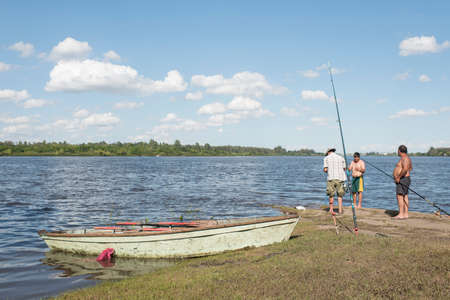 Mercedes, Soriano / Uruguay; Dec 26, 2018: summer landscape on the bank of the Rio Negro: three men fishing with rods next to a rowboat.