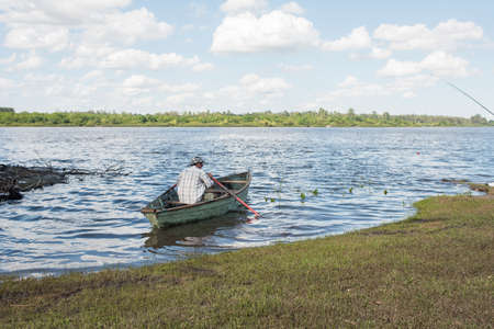 Mercedes, Soriano / Uruguay; Dec 26, 2018: summer landscape on the bank of the Rio Negro: grassy shore, calm water and a man sailing in a rowboat. Editorial