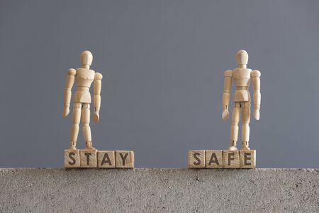 Image about the need for self-care, in relation to the coronavirus outbreak, covid-19. Pair of wooden human figures standing on cubes with the text Stay Safe Stockfoto