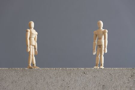 Conceptual image about social distancing, mandatory due to the coronavirus outbreak, covid-19. Pair of wooden human figures standing looking at each other from a safe distance.