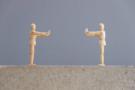 Image about social distancing, mandatory due to the coronavirus outbreak, covid-19. Pair of wooden human figures standing at a safe distance from each other.