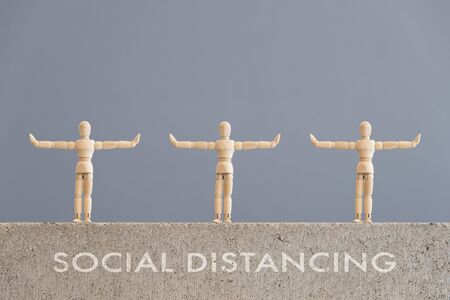 Image about social distancing, mandatory due to the coronavirus outbreak, covid-19. Three wooden human figures standing with arms out to the sides, at a safe distance from each other; and text.