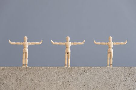 Image about social distancing, mandatory due to the coronavirus outbreak, covid-19. Three wooden human figures standing with arms out to the sides, at a safe distance from each other.