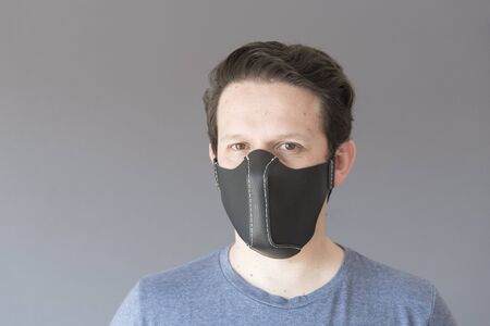 Front portrait of a young man wearing a homemade reusable synthetic leather protective face mask, to prevent the spread of the coronavirus disease, in the context of the covid-19 outbreak.