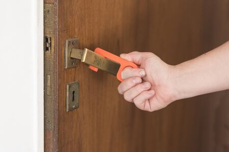 Young man using a contactless tool to open a door, to avoid the spread of the coronavirus disease, Covid-19. New normal.