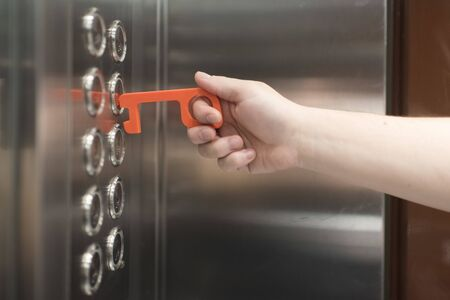 Young man using a contactless tool to press an elevator button, to avoid the spread of the coronavirus disease, Covid-19. New normal.