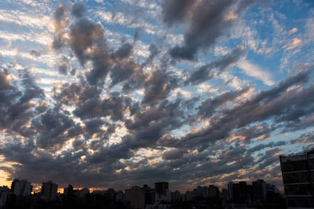 Skyline of Buenos Aires, Argentina, with a dramatic sunset sky. Dark gray and white clouds over a blue sky, unique cloudscape Фото со стока