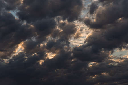 Cloudscape, sky full of dark gray clouds at sunset