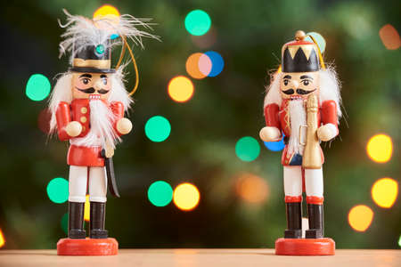 Pair of traditional red and white Christmas nutcrackers with a green background with colored lights out of focus