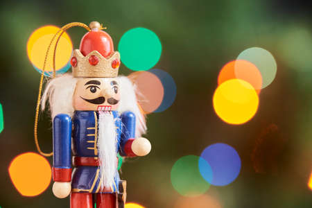 Traditional colorful wooden Christmas nutcracker with a green background with colored lights out of focus, copy space