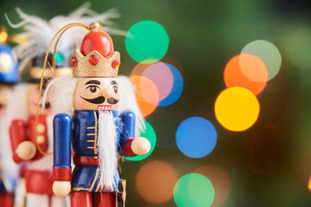 Traditional colorful Christmas nutcrackers with a green background with colored lights out of focus, copy space Stock Photo