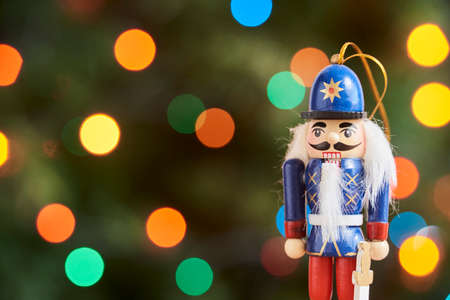 Traditional colorful wooden Christmas nutcracker with a green background with colored lights out of focus, copy space Stock Photo
