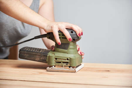 Carpentry work, detail of a young caucasian woman with her nails done sanding wood, using an electric sander.