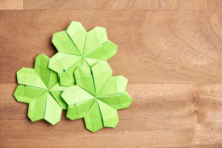Origami four-leaf clovers, made of light green paper, on a wooden background. Concepts of luck and St. Patrick's Day. Image with copy space.