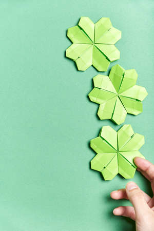 Origami four-leaf shamrocks, made of light green paper, on green background. A young hand is placing one of the clovers at the bottom. Concepts of luck and St. Patrick's Day. Image with copy space.
