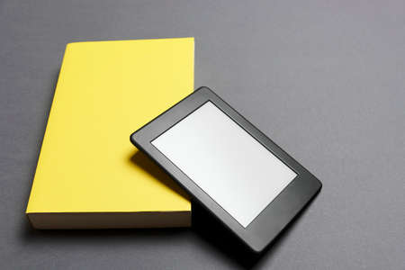 Electronic reader with blank screen and closed yellow book on gray background. Concepts of technology and reading. Image with copy space.