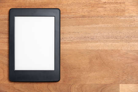 Electronic reader with blank screen on a wooden surface. Concepts of technology and reading. Image with copy space.
