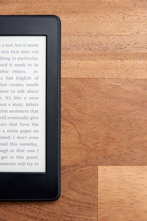 Closeup image of an electronic reader with blank screen on a wooden surface. Concepts of technology and modernity. Image with copy space.