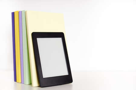 Colored books with blank spine and an electronic reader on a white shelf with white background. Concepts of technology, reading and education. Bright image with copy space.
