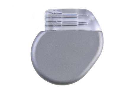 A cardiac pacemaker (~ 8mm thin, volume 12cc, 26 grams, implantable) to help regulate abnormal rhythms. (12MP camera, isolated, macro)